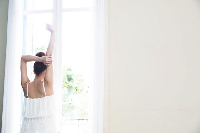 腕を伸ばし窓を覗く女性