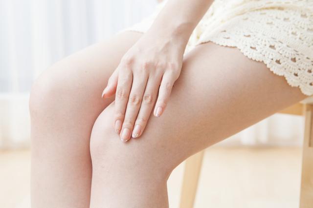 ファンデーションで足の黒ずみを隠す女性