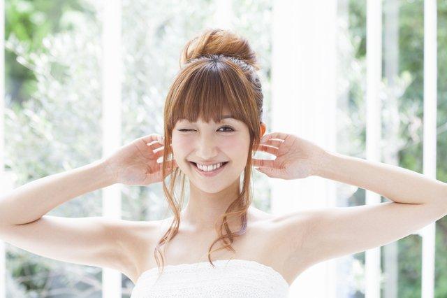 白いテラスを背景に掌を耳にあてて微笑む女性
