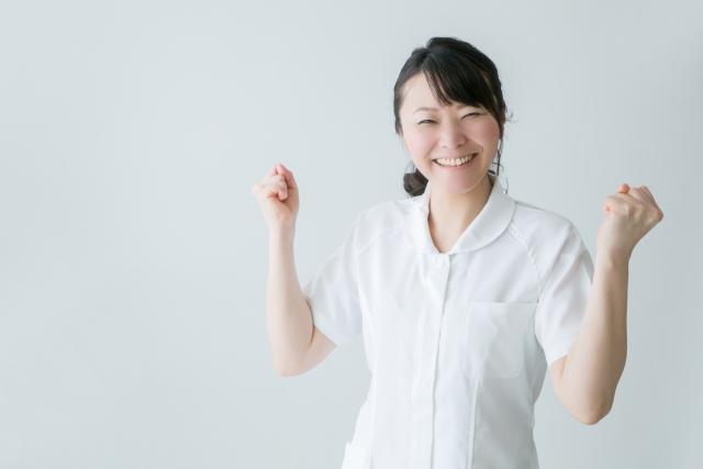 ガッツポーズする白衣の女性